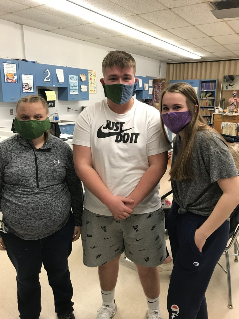 Three students modeling their clamshell masks they made in class.
