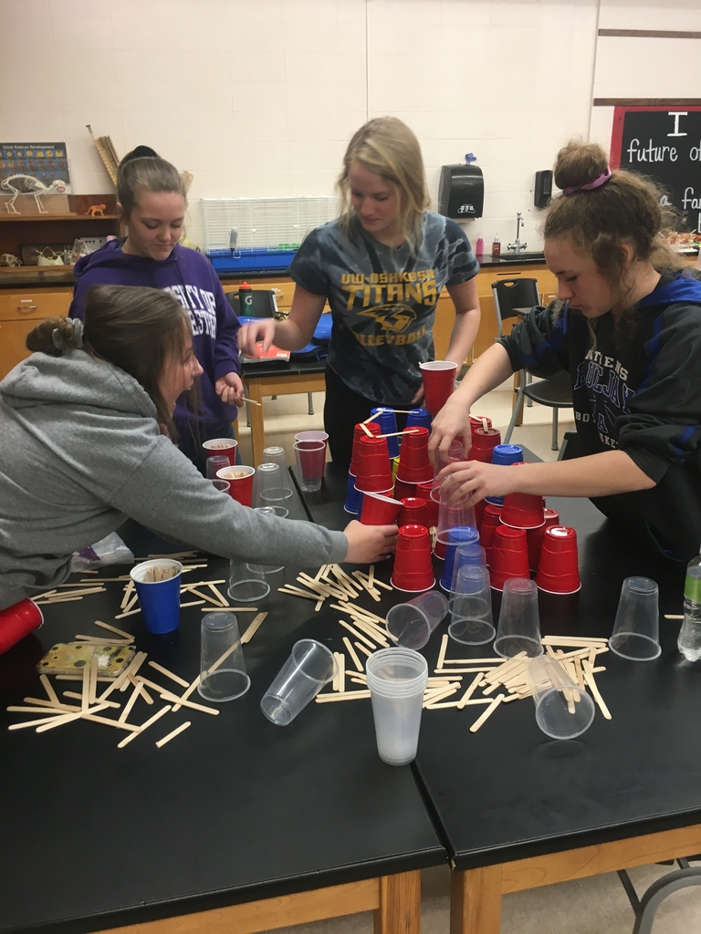 Students trying to rebuild their tower after life through something at them.